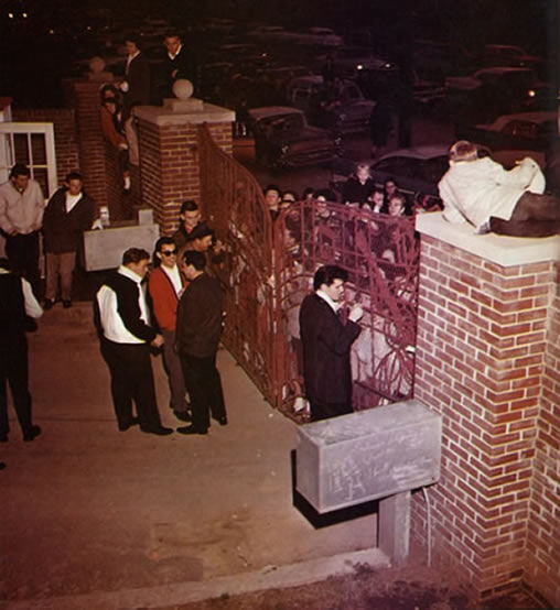 Elvis signing autographs at the Graceland gates.